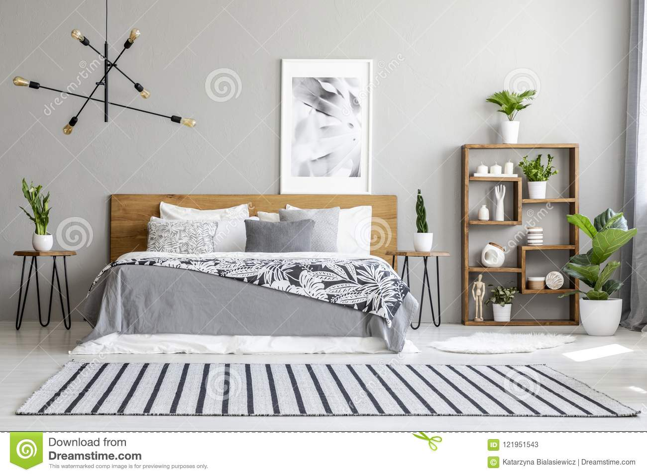 Striped carpet near bed with patterned blanket in bedroom interi