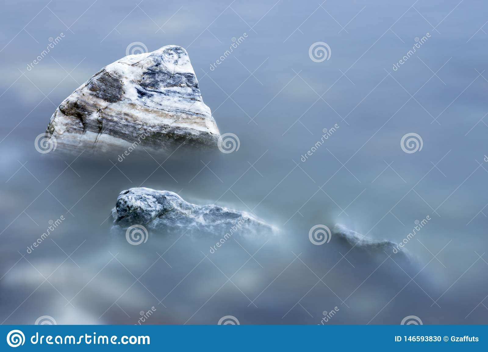 Striped rocks in smooth blue water