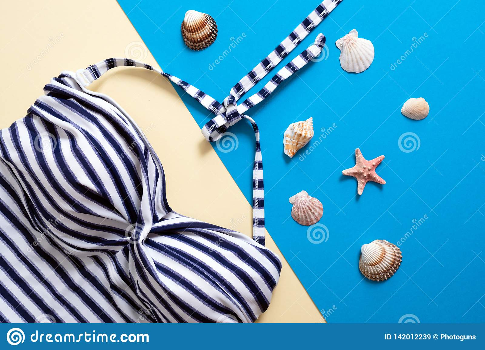 Striped women`s swimsuit and sea shells on blue and yellow background. Flat lay composition, concept of summer holidays, vacation