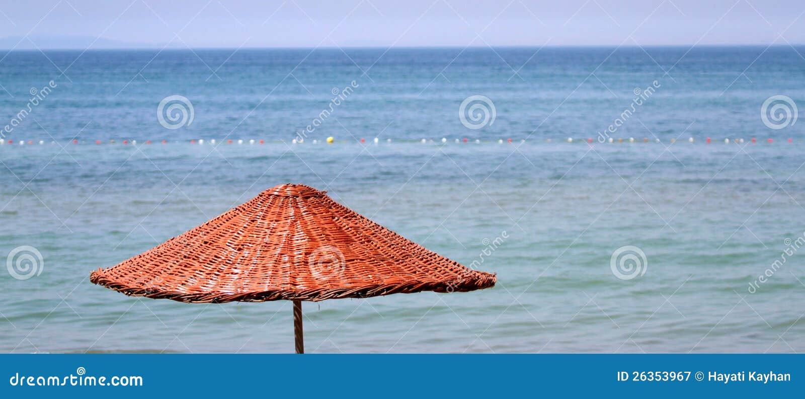 Strohregenschirm auf einem Strand