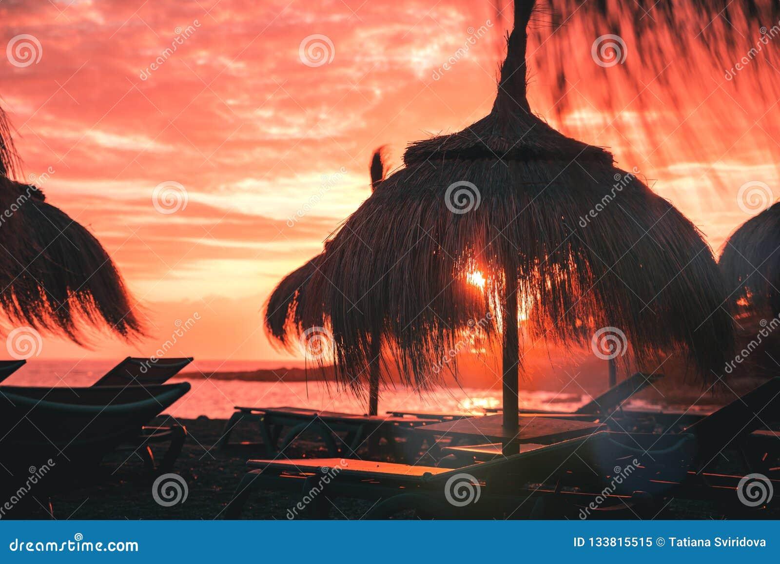 Strohstrandschirm bei korallenrotem Sonnenuntergang