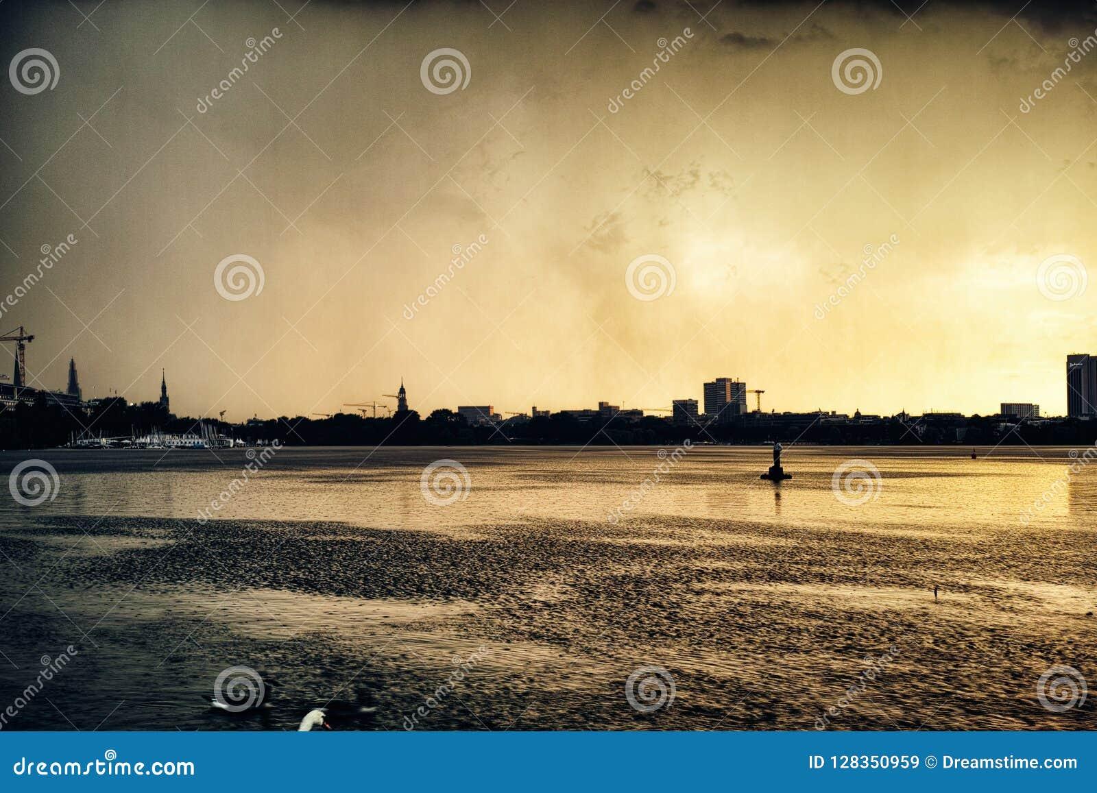 Strom Alster jezioro w Hamburskiego Niemcy kaczki miasta sławnego parka żeglowania panoramy nieba nocy chmury zmierzchu dramatycz