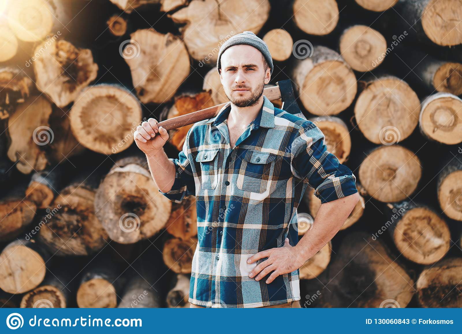 Strong bearded lumberman wearing plaid shirt holds axe on his shoulder