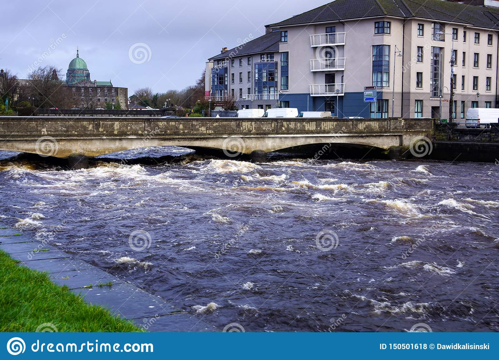 Strong current on river that about to go over bridge and riverbanks in Galway