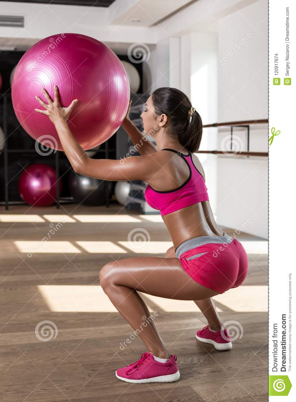 Strong female squatting on fitness mat with weight medicine ball in health club.