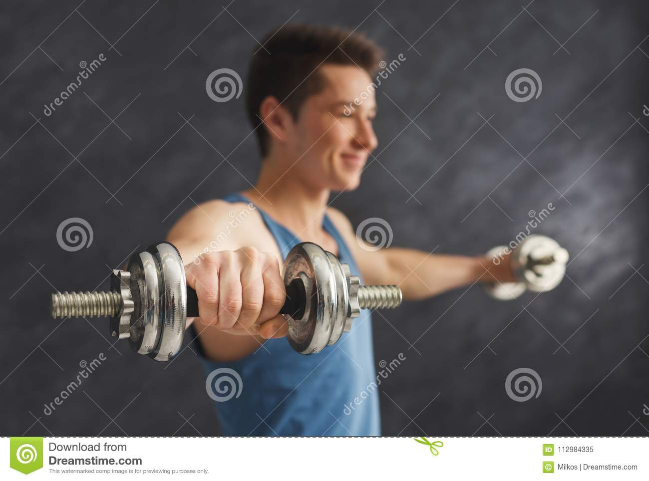 Fitness man making exercise with dumbbells