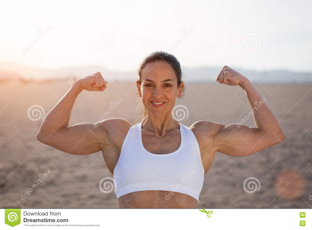 Strong Fitness Woman Flexing Biceps On Sunset