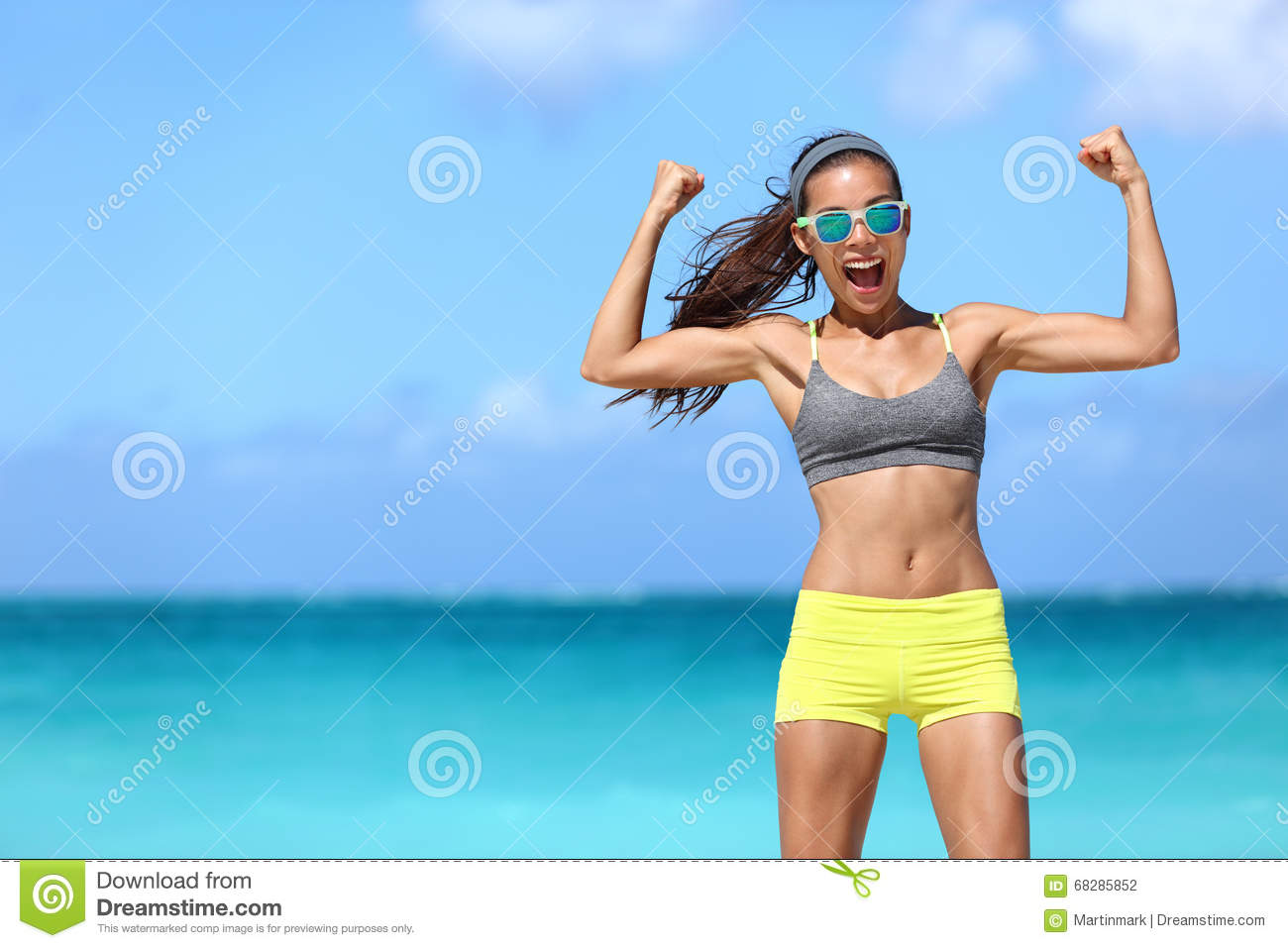 Strong fitness woman having fun showing off muscular arms