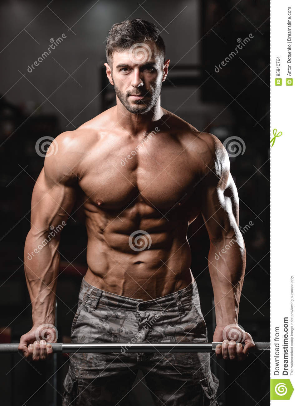 Strong and handsome athletic young man muscles abs and biceps