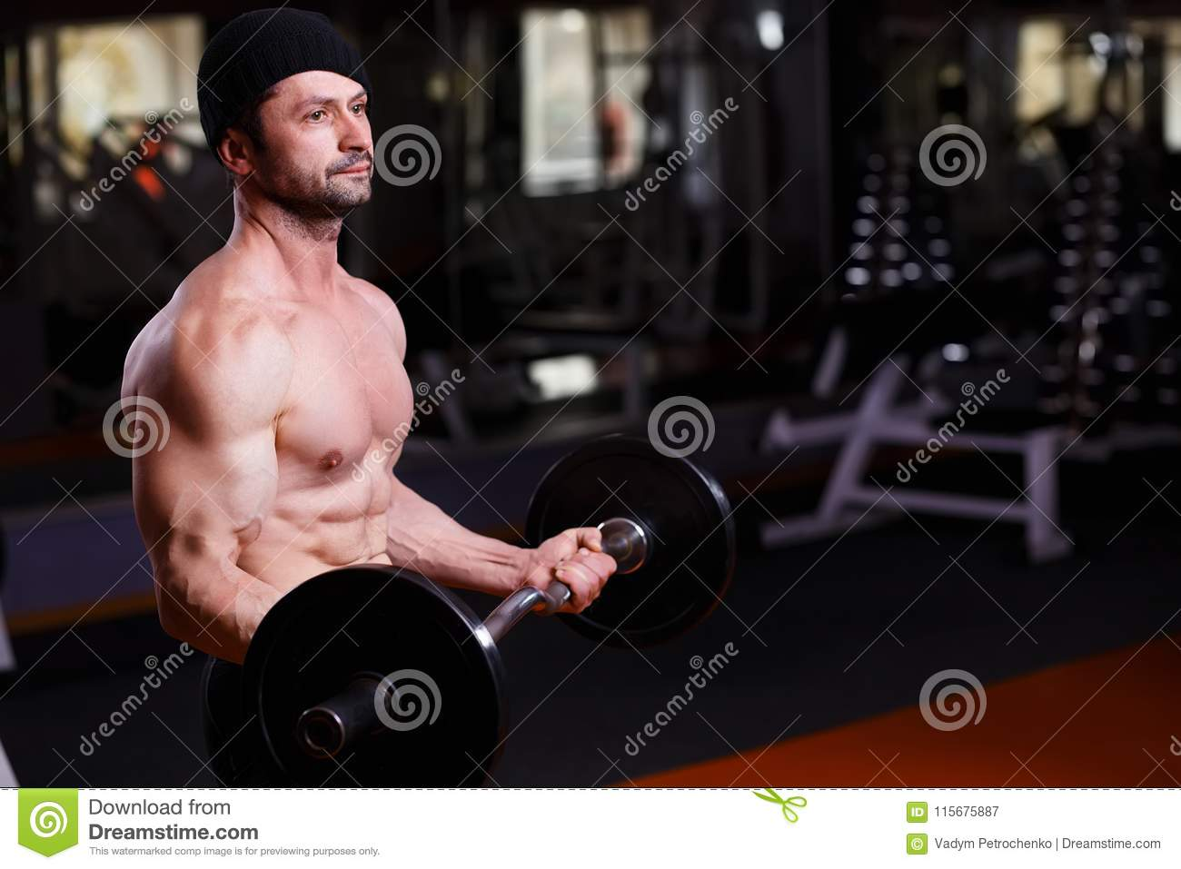 Strong healthy adult ripped man with big muscles training with b