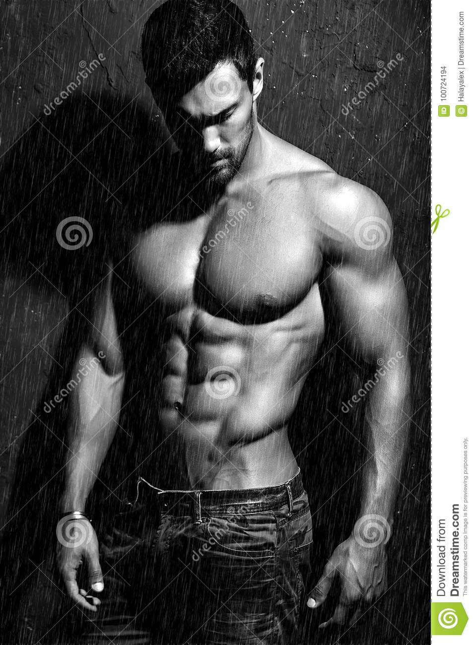 Strong healthy handsome Athletic Man Fitness Model posing near dark gray wall
