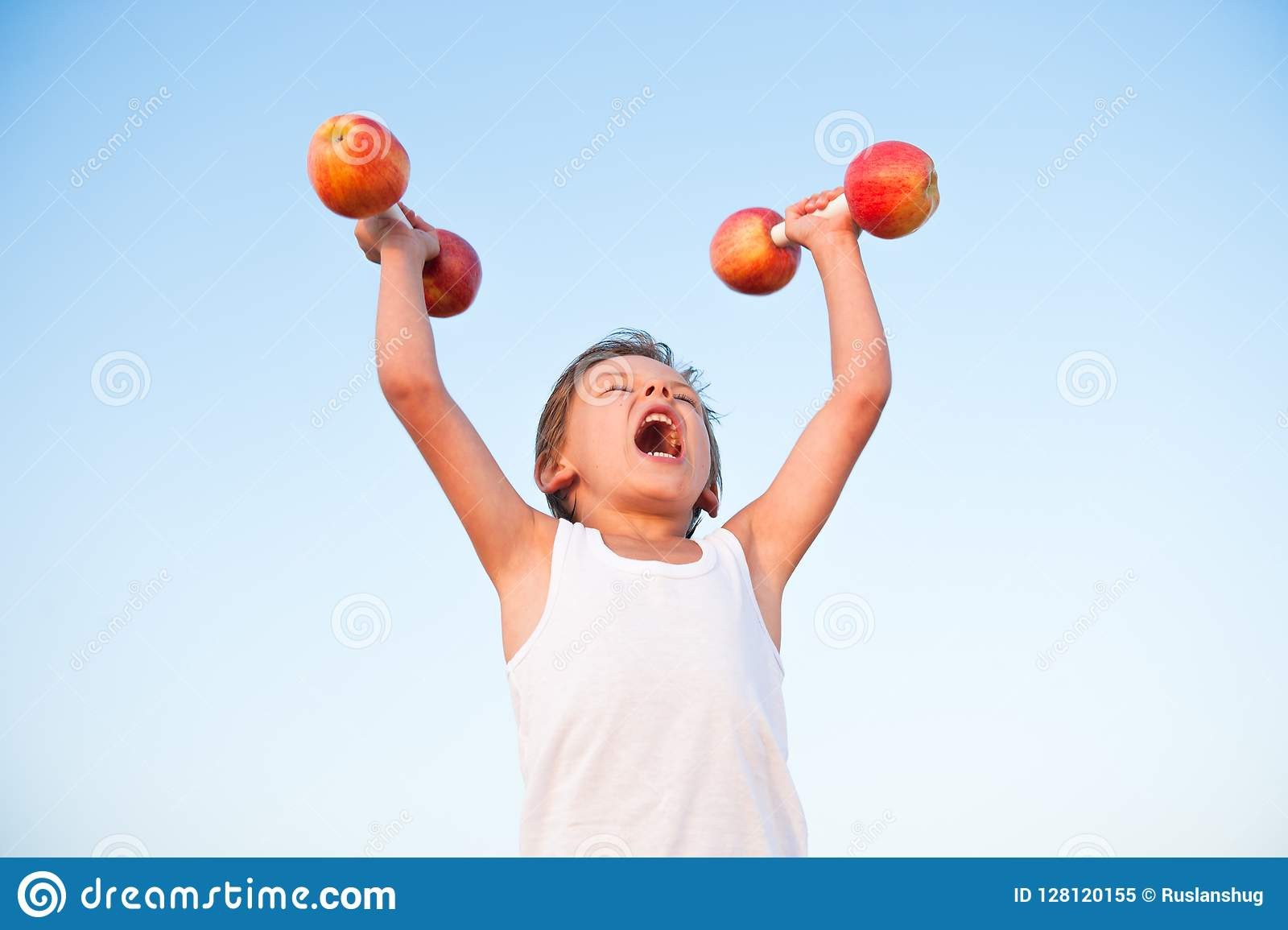 Strong healthy kid in white shirt lifting dumbbells made from ap