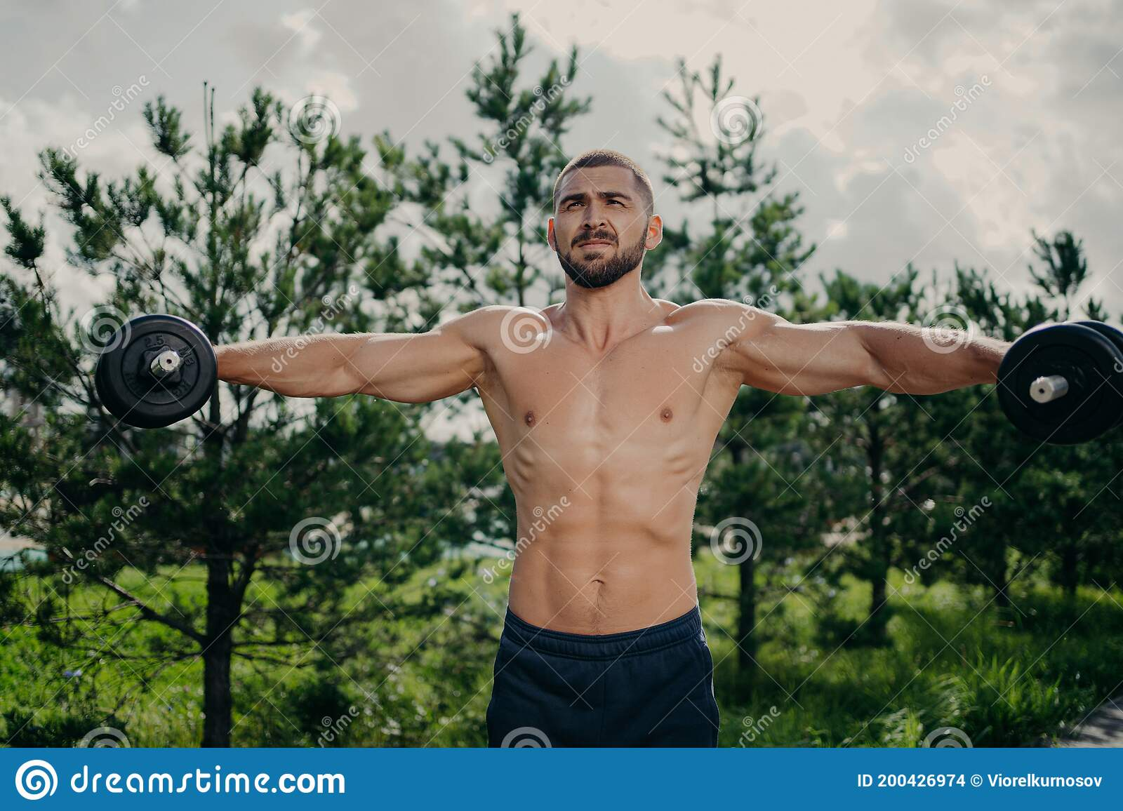 Muscular Strong Athletic Man With Naked Torso Pumping Up