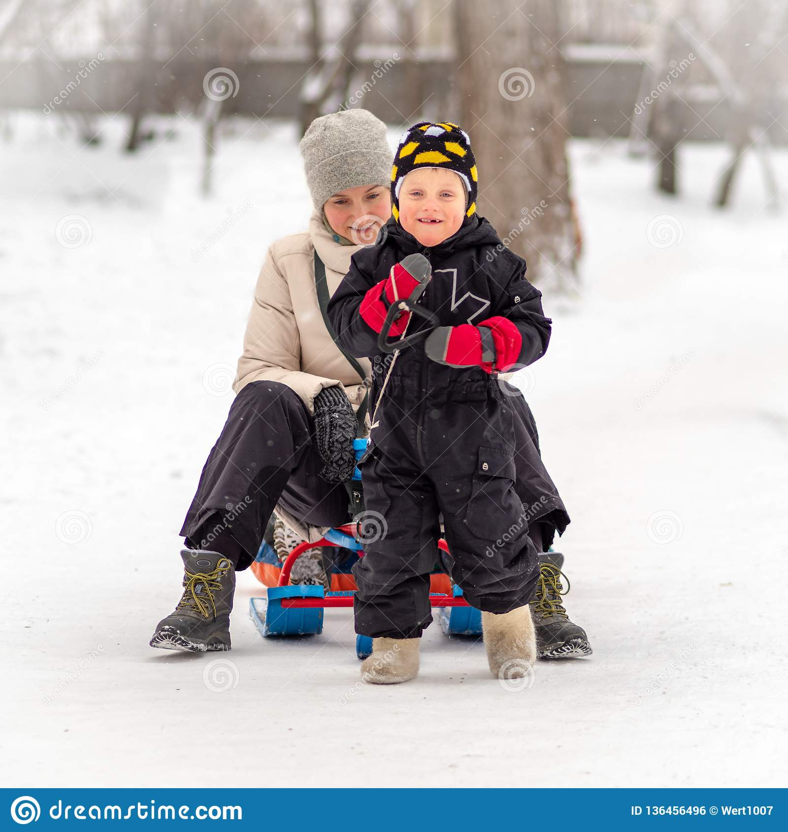 Strong little boy carries his mother on a sled