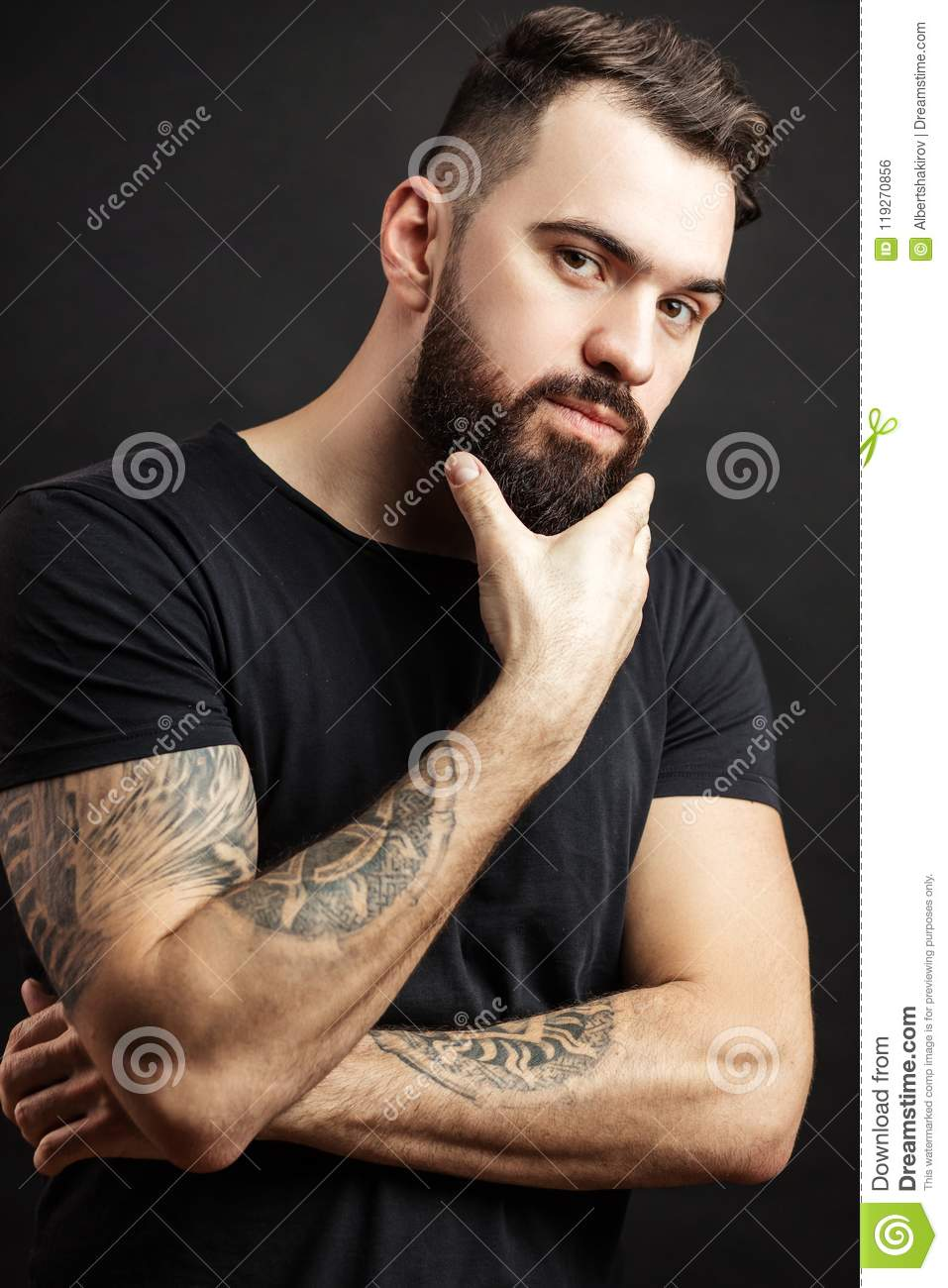 Strong man in black tight fitted shirt with a serious expression on his face.