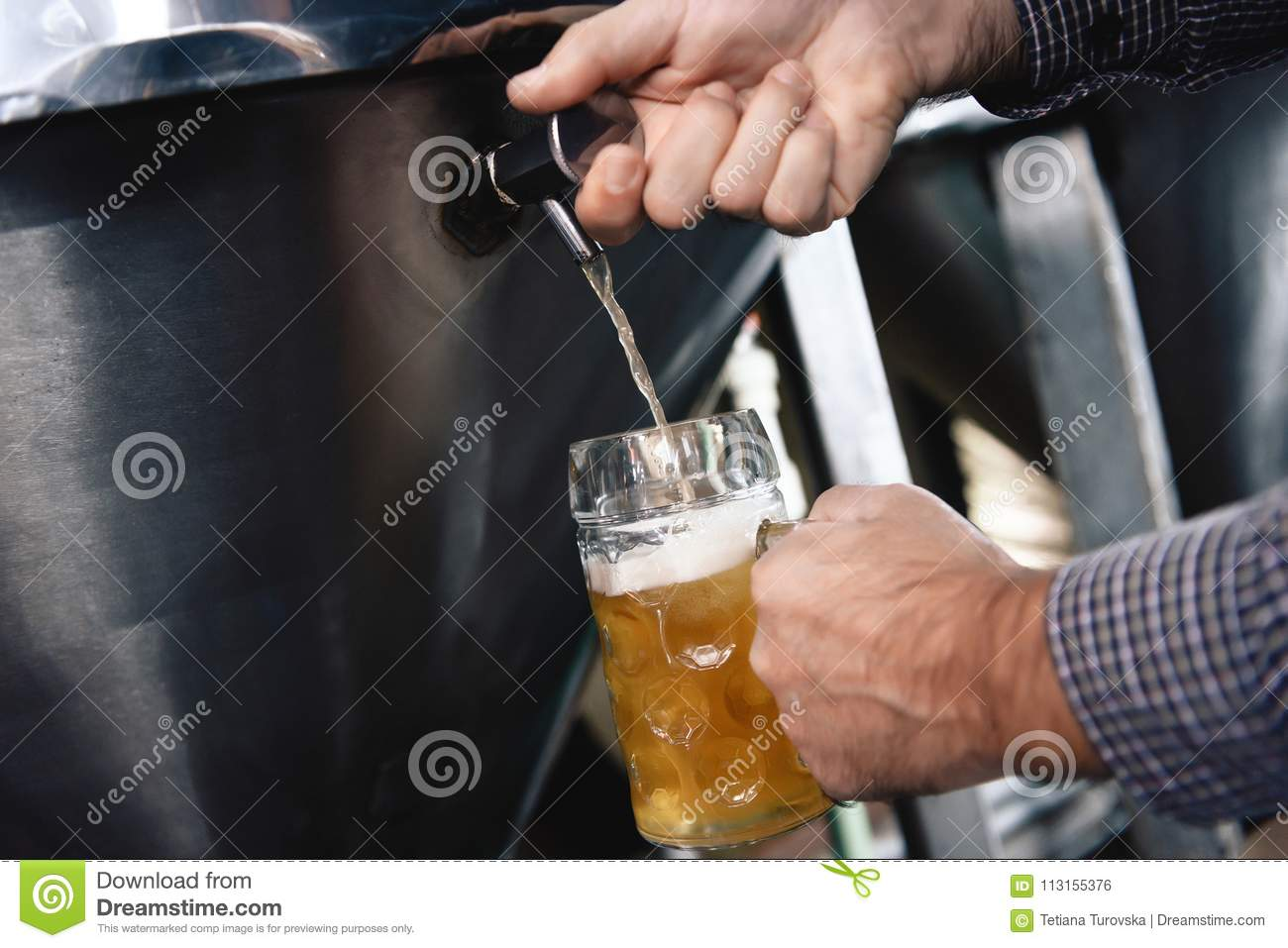 Strong man`s hands pour beer in tumbler from beer tap at craft brewery.