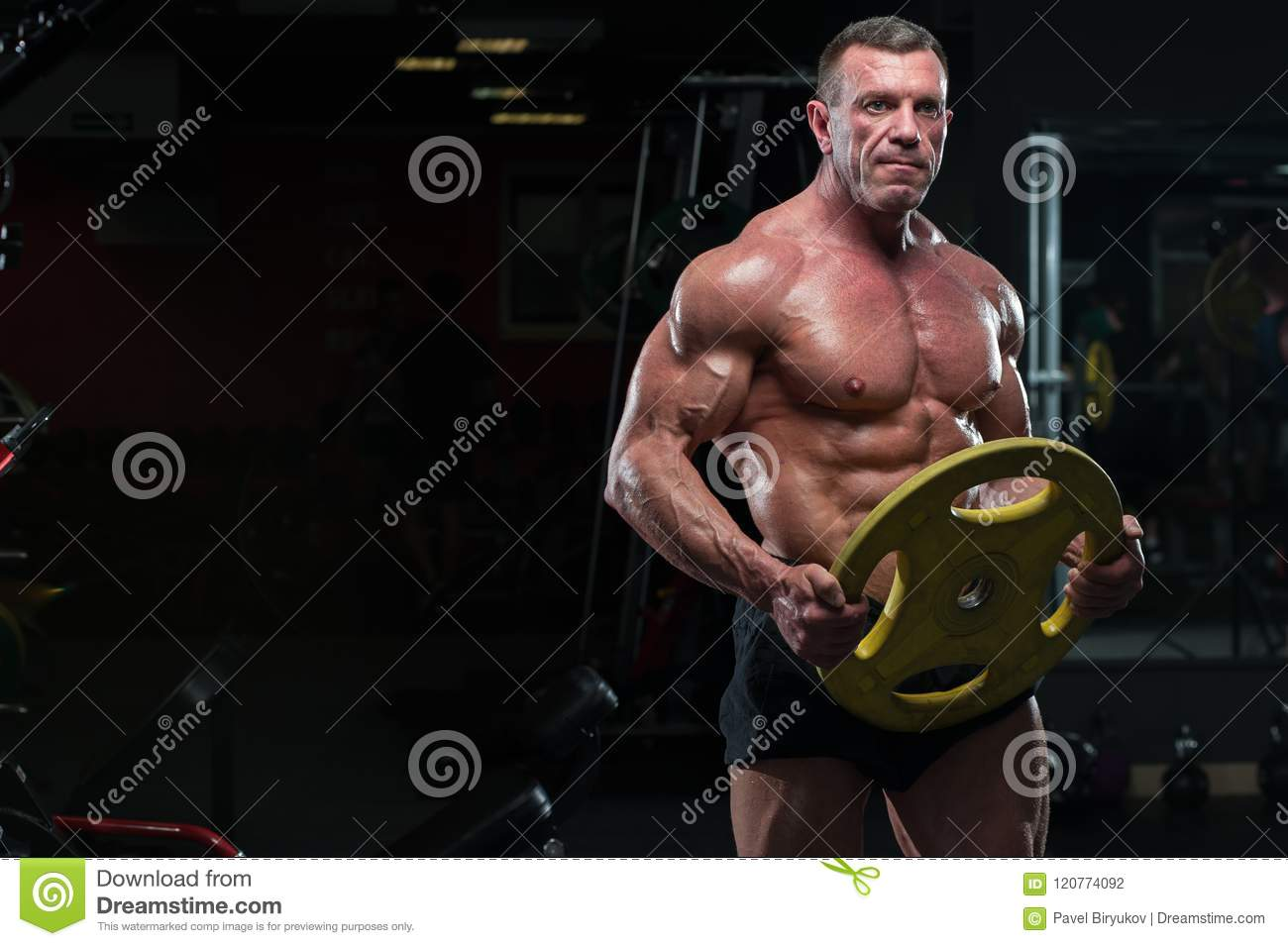 Strong mature man with relief body posing in gym
