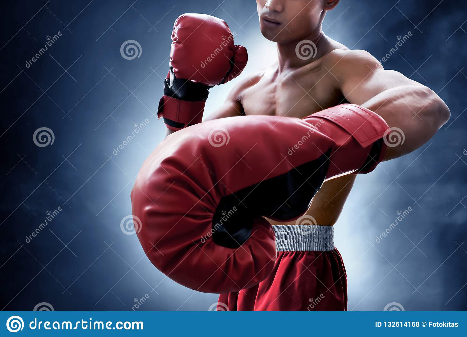 Strong muscular boxer on smoke background