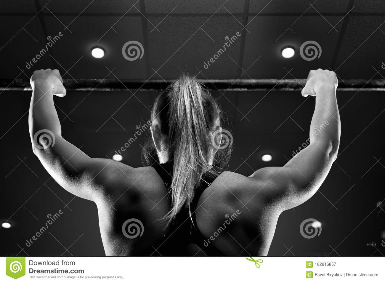 Strong muscular female doing pull up in gym