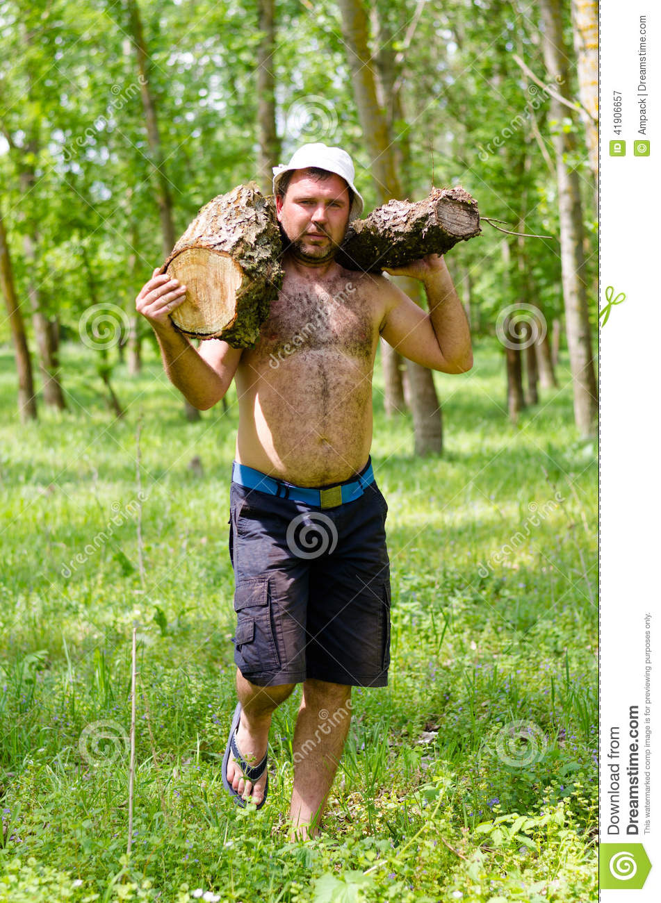strong muscular man carrying a large log of wood stock. Black Bedroom Furniture Sets. Home Design Ideas