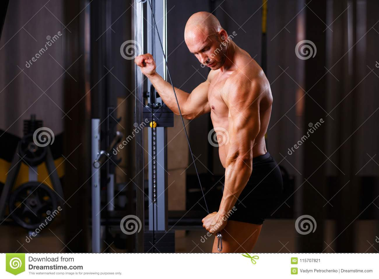 Strong ripped bald man bodybuilder working out with equipment in