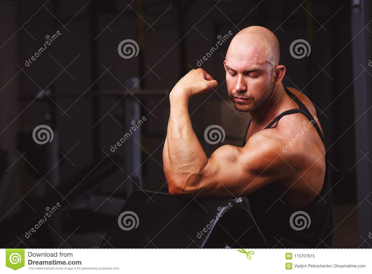 Strong ripped bald man demonstrating big muscles in gym. Sport,