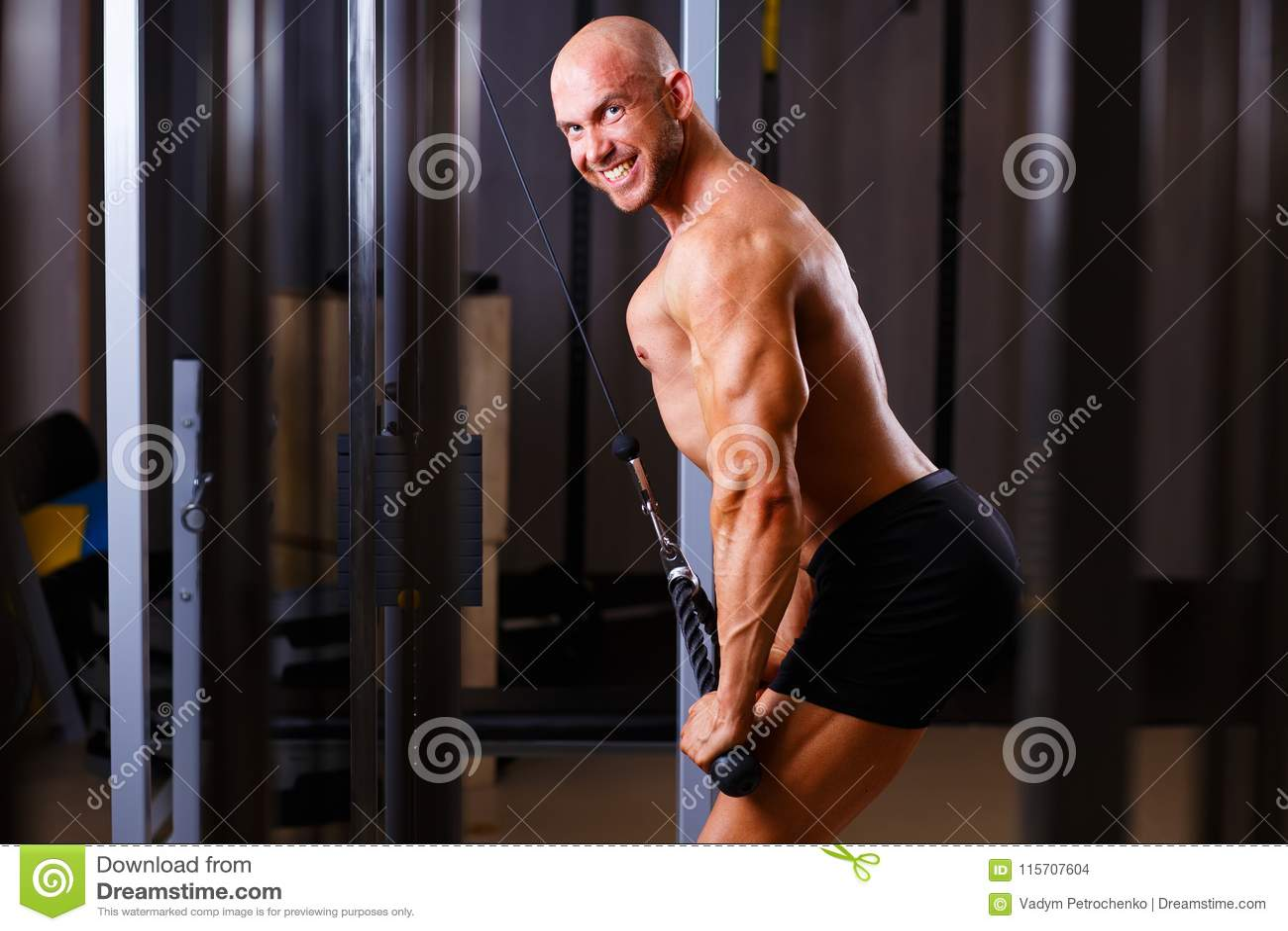 Strong ripped bald man pumping iron. Sports man bodybuilder smil