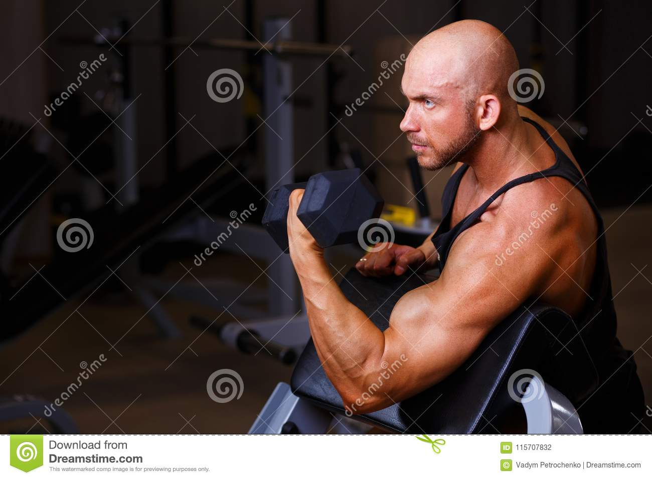 Strong ripped bald man pumping iron. Sports man working out with