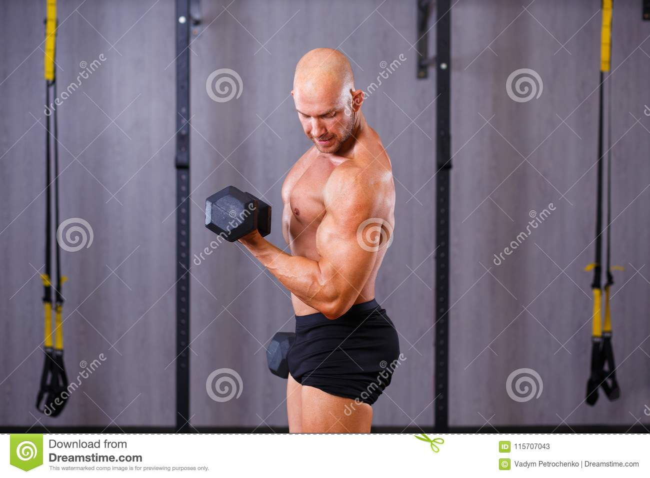 Strong ripped bald man working out with dumbbells in gym. Sport,