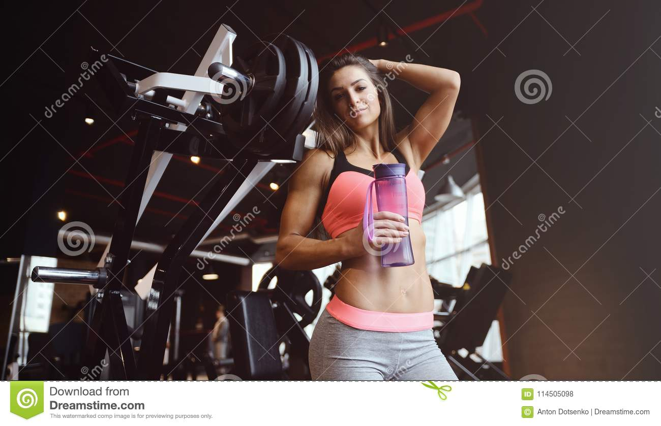 ad65c30656fc8 Beautiful strong athletic muscular young caucasian fitness girl water  bottle workout training in the gym on diet pumping up abs muscles and  posing ...