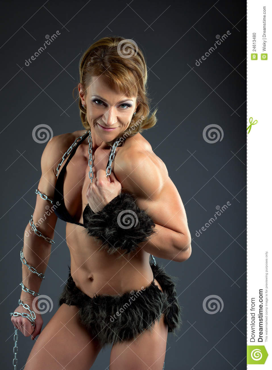Strong athletic woman body builder posing in amazon fur costume with