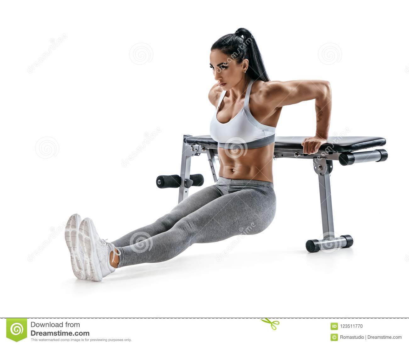 Strong woman working out arms muscles doing triceps dips using bench.