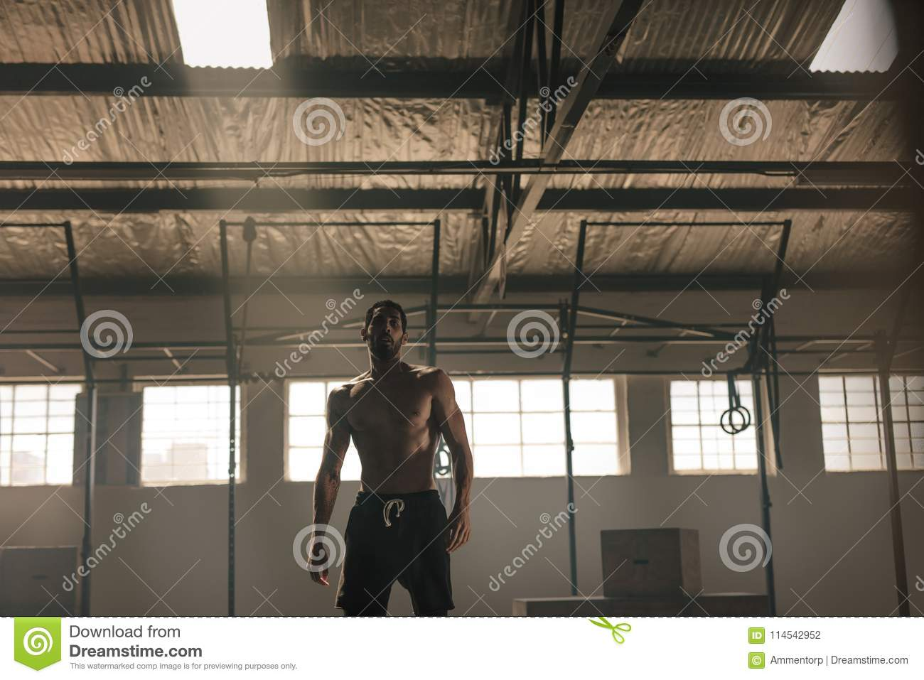 Strong young man with muscular body in gym