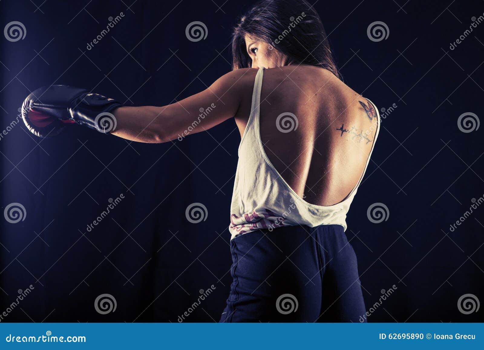 Strong young woman boxing performing a jab kick