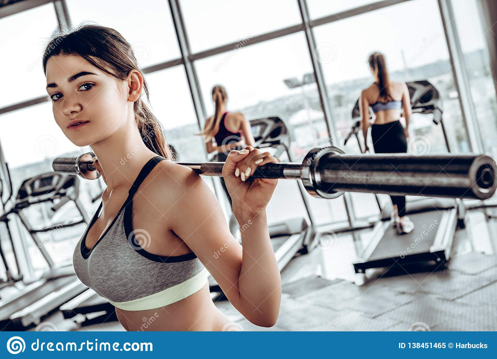 Strong young woman with beautiful athletic body doing exercises with barbell