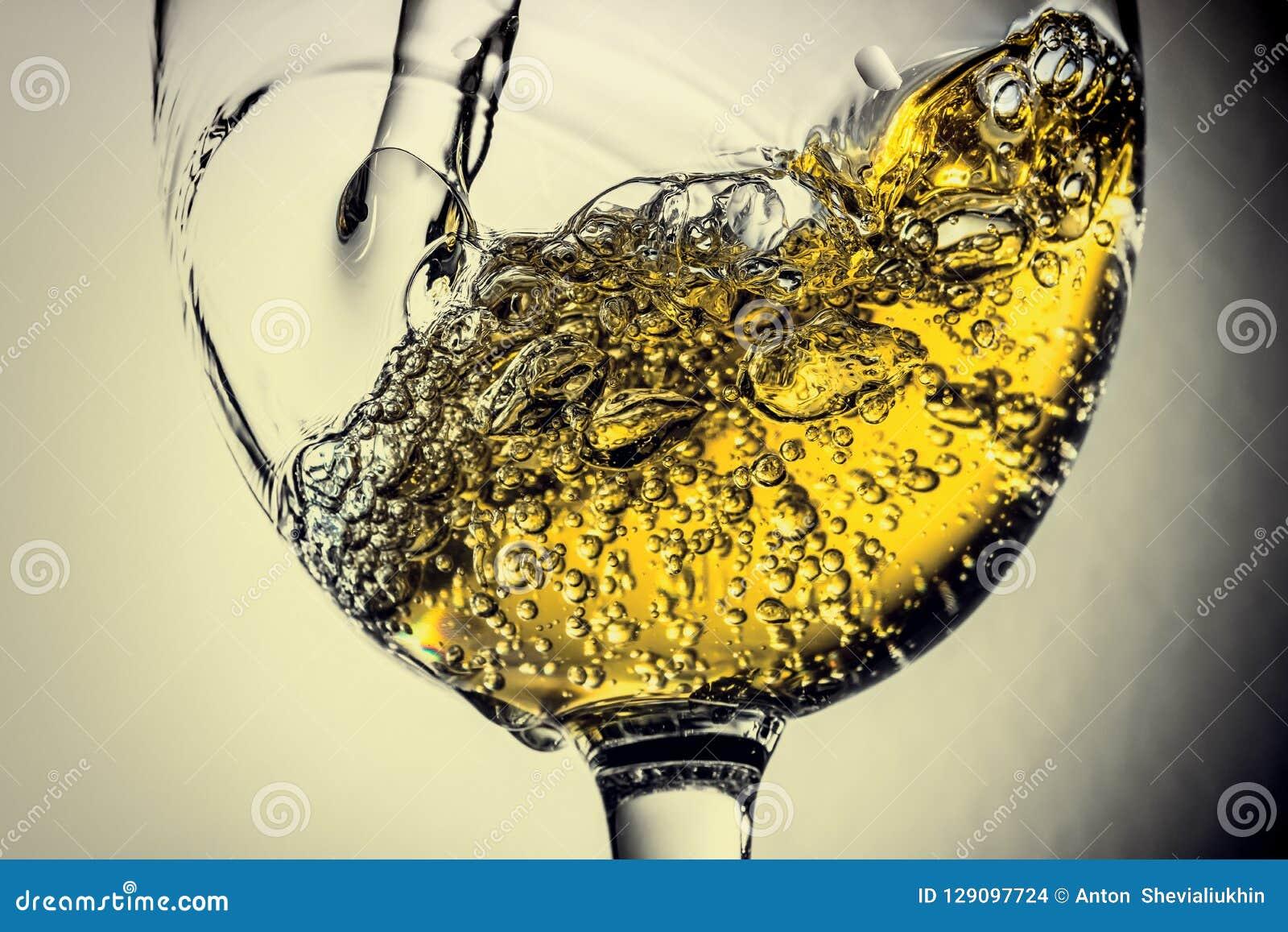 Stroom van het witte wijn gieten in een glas, het witte close-up van de wijnplons Zwart-witte foto met kleur van wijn