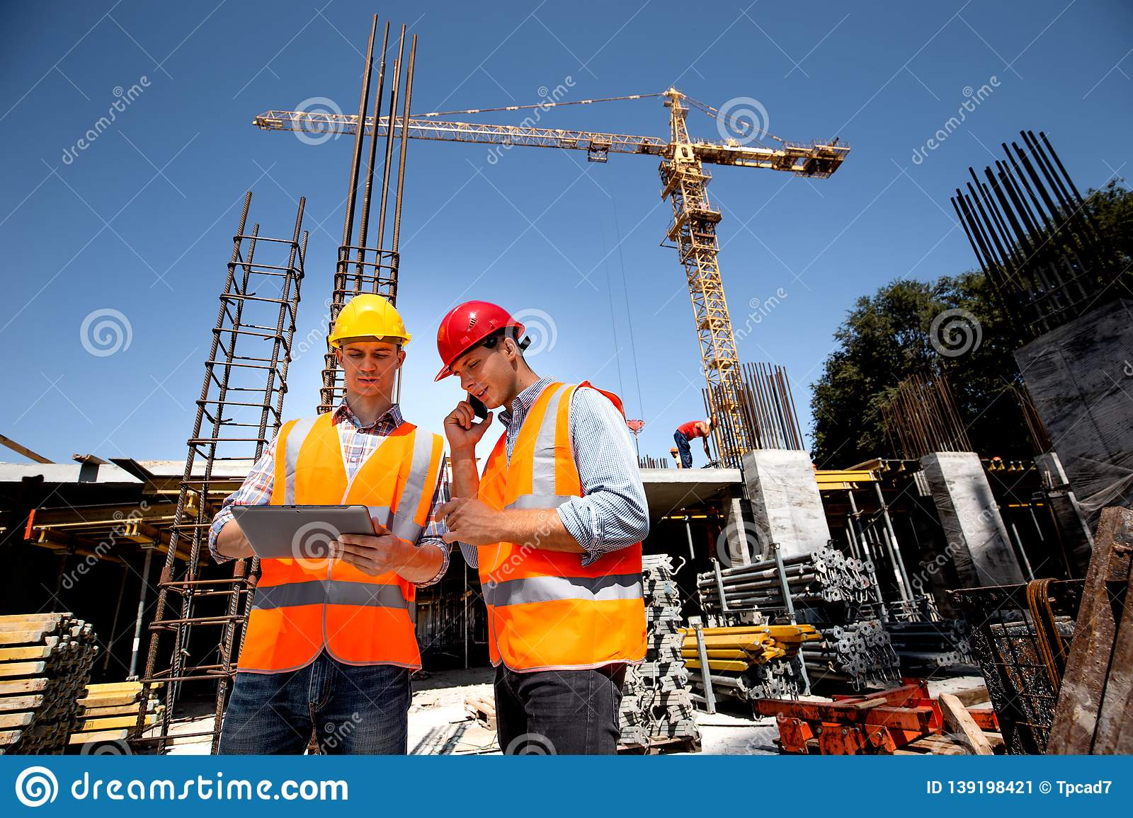 Structural engineer and architect dressed in orange work vests and hard hats discuss the construction process by the