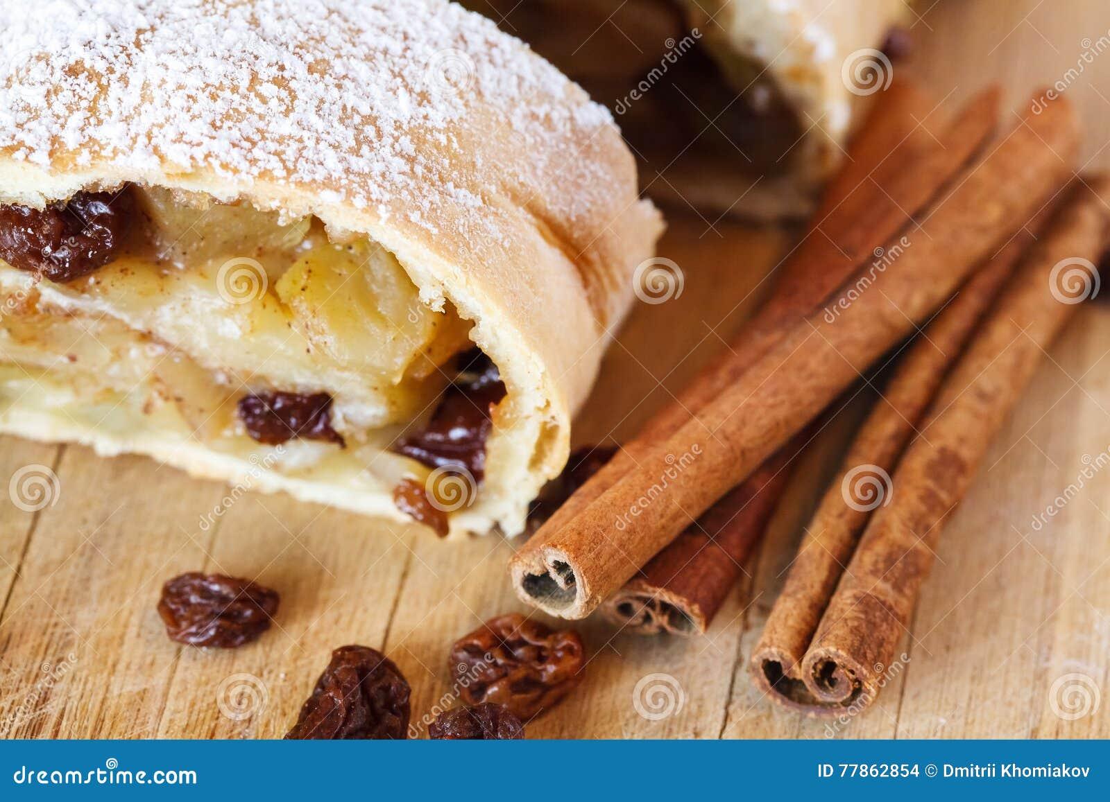 Strudel της Apple με τη ζάχαρη τήξης, ραβδιά κανέλας, ξύλινο υπόβαθρο
