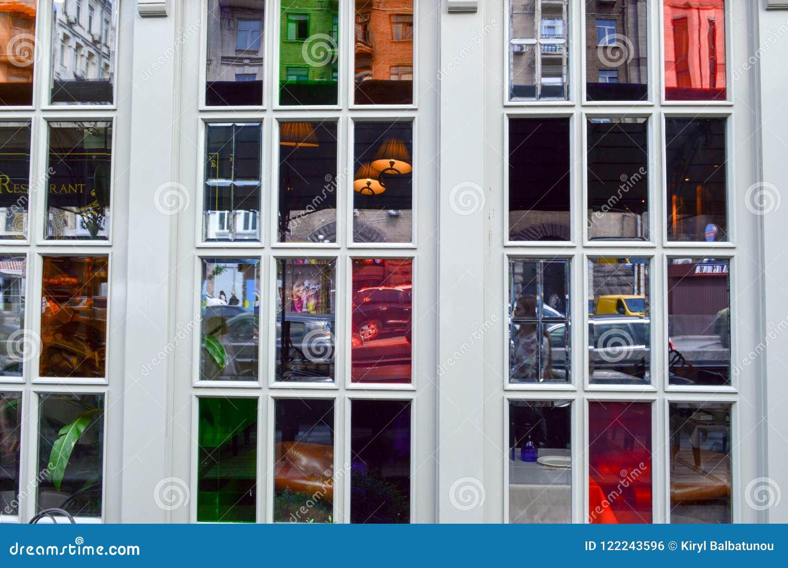 Struttura dei vetri multicolori di una bella finestra, finestre di vetro macchiato nella via con le strutture di legno bianche I