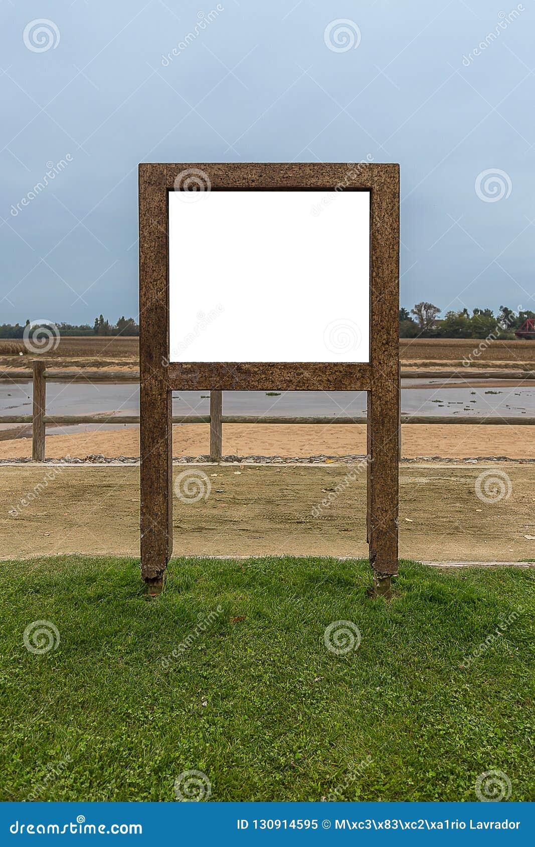 Struttura di pubblicità di legno dal fiume, in un campo di erba sotto Pale Sky