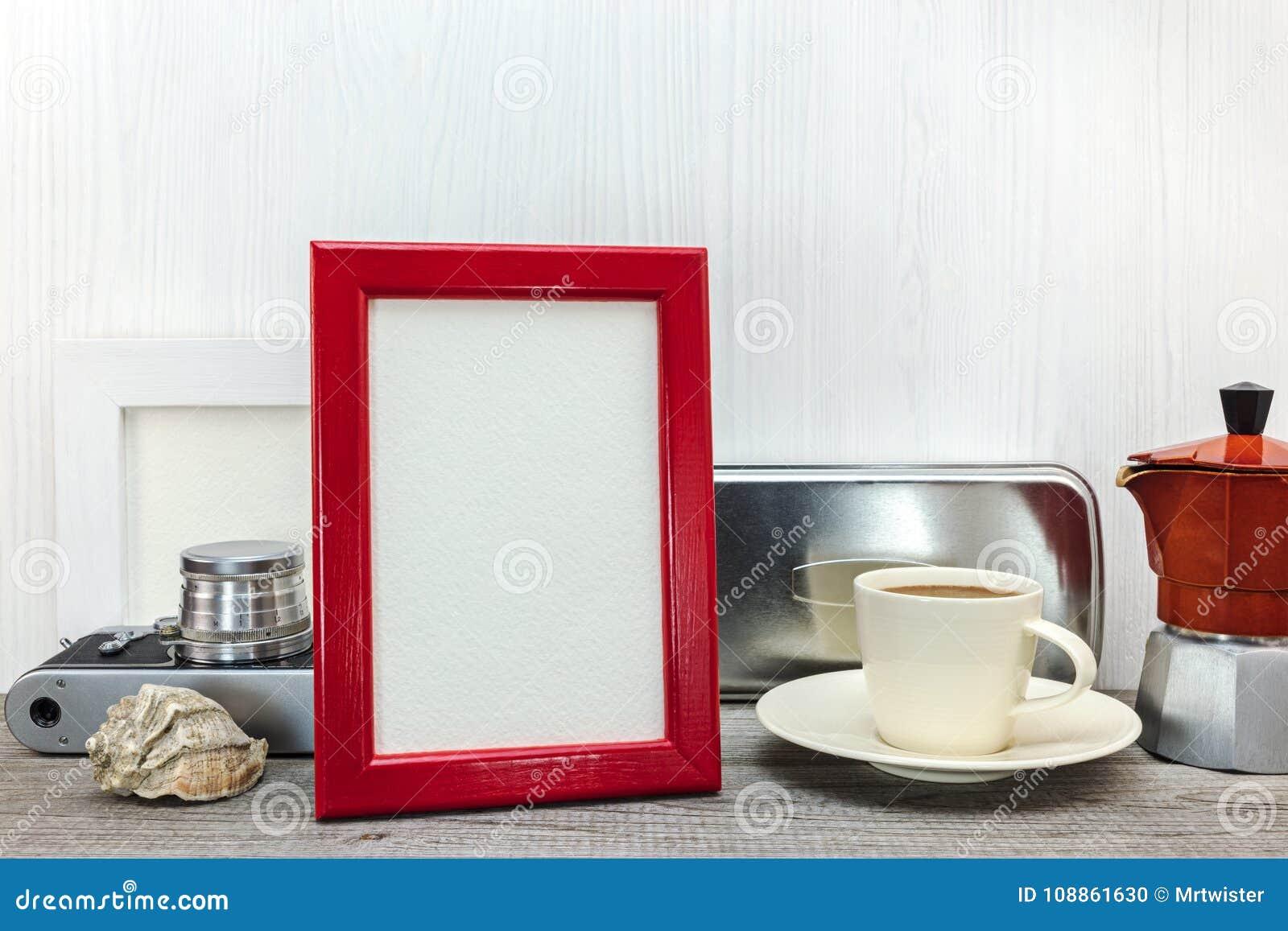 Struttura e caffettiera rosse della foto con la tazza sul backgrou di legno bianco