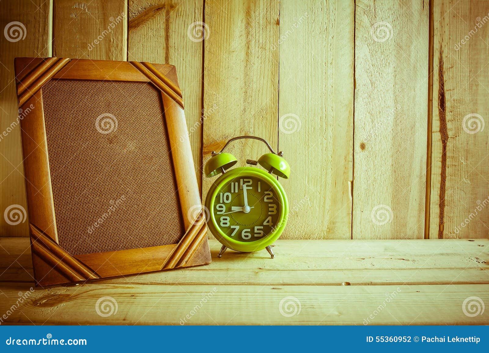 Struttura ed orologio antichi della foto sulla tavola di legno sopra fondo di legno