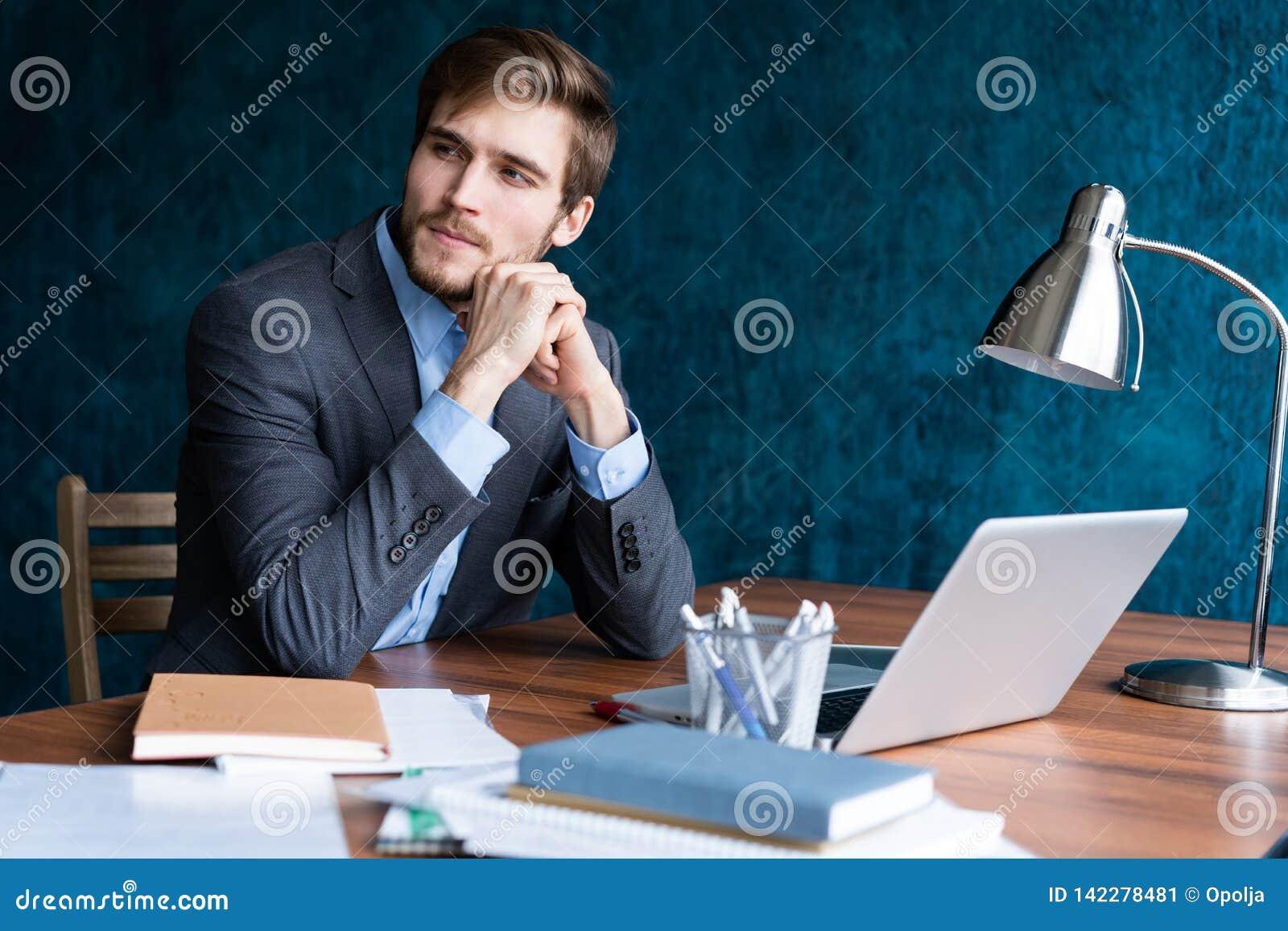 Strzał młodego człowieka obsiadanie przy stołowy patrzeć oddalony i główkowaniem Rozważny biznesmena obsiadanie w biurze