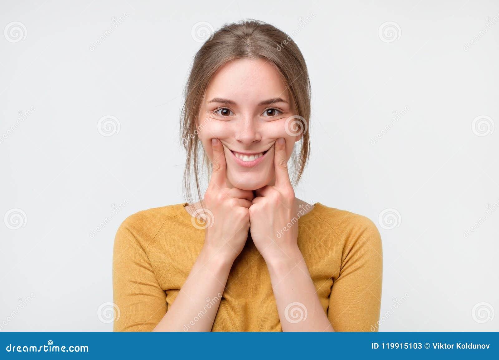 Strzał piękna caucasian nastoletnia dziewczyna zmusza uśmiech, trzyma ona przy krawędziami jej wargi palce