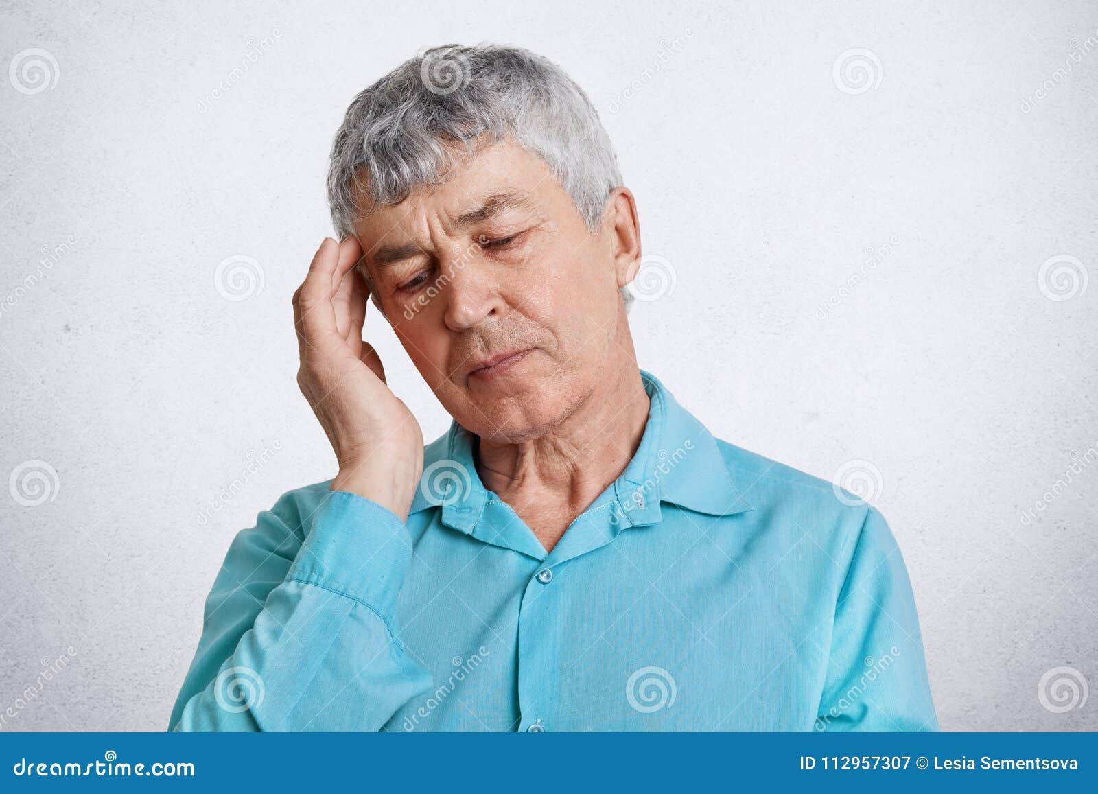 Strzelają zmęczony starszy męski emeryt, utrzymań oczy zamykający, ręka na świątyni, są ubranym formalną błękitną koszula, migren