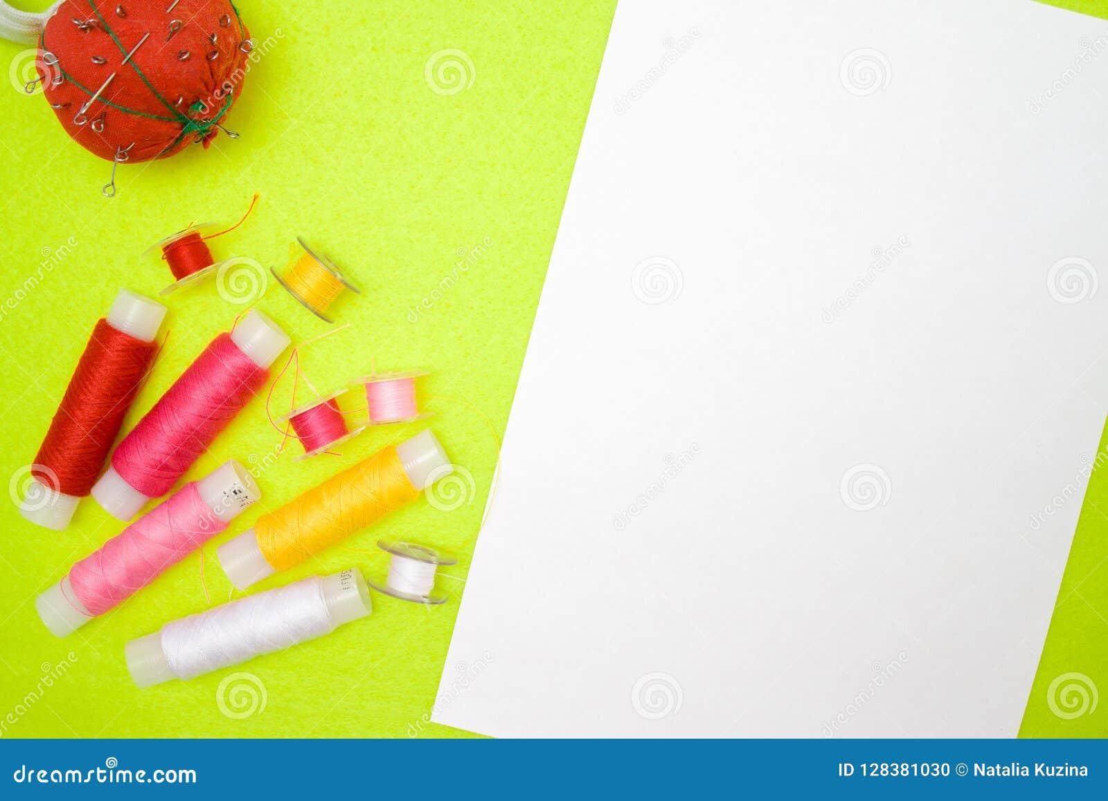 Stubarwnych nicianych zwitki czerwieni menchii biała i pomiarowa żółta taśma na zielonym tle Szyć dostawy i akcesoria dla igły