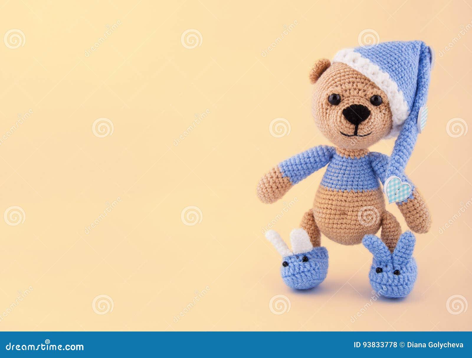 Stucken nallebjörn i ett lock och häftklammermatare på en försiktig gul bakgrund Leksaker som göras av handen En mjuk gåva kopier