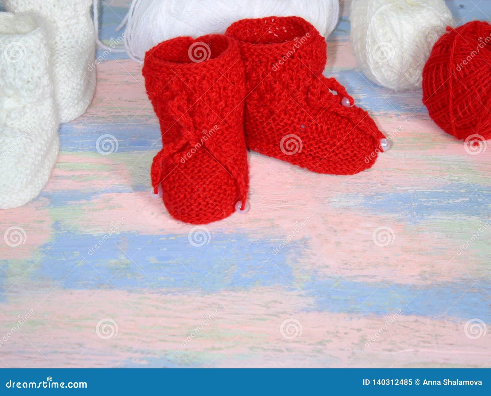 Stuckit rött behandla som ett barn byten, röda och vita bollar av ullgarn för att sticka på ett rosa - blå bakgrund