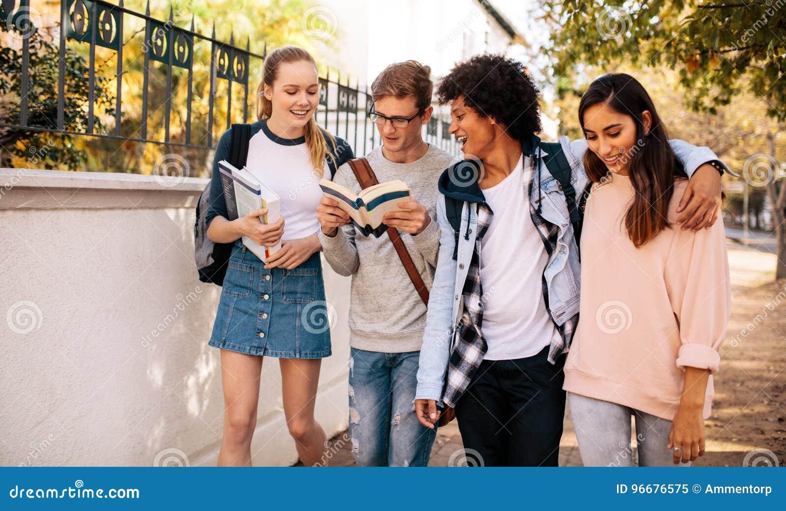 Studenci uniwersytetu z książkami w szkoła wyższa kampusie