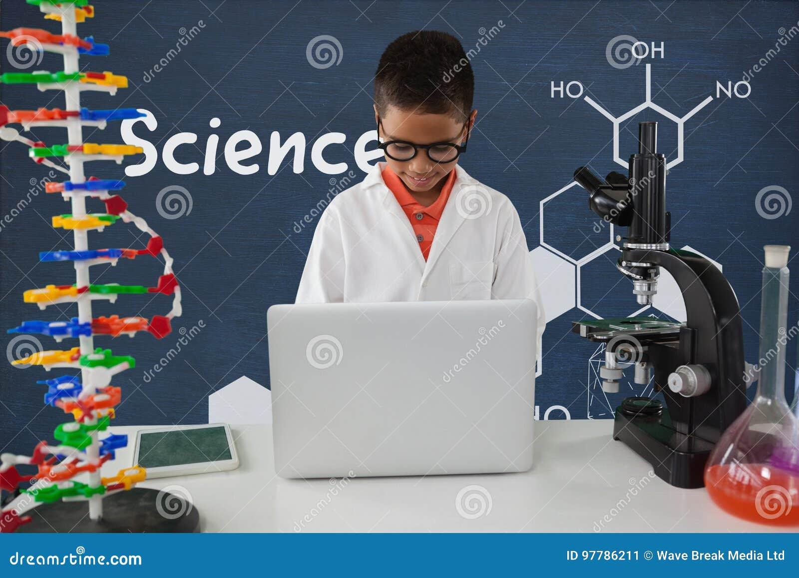 Studencka chłopiec przy stołem używać komputer przeciw błękitnemu blackboard z nauk grafika i tekstem